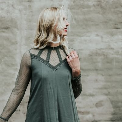 Blonde woman in green top touching hair and gazing to the right.
