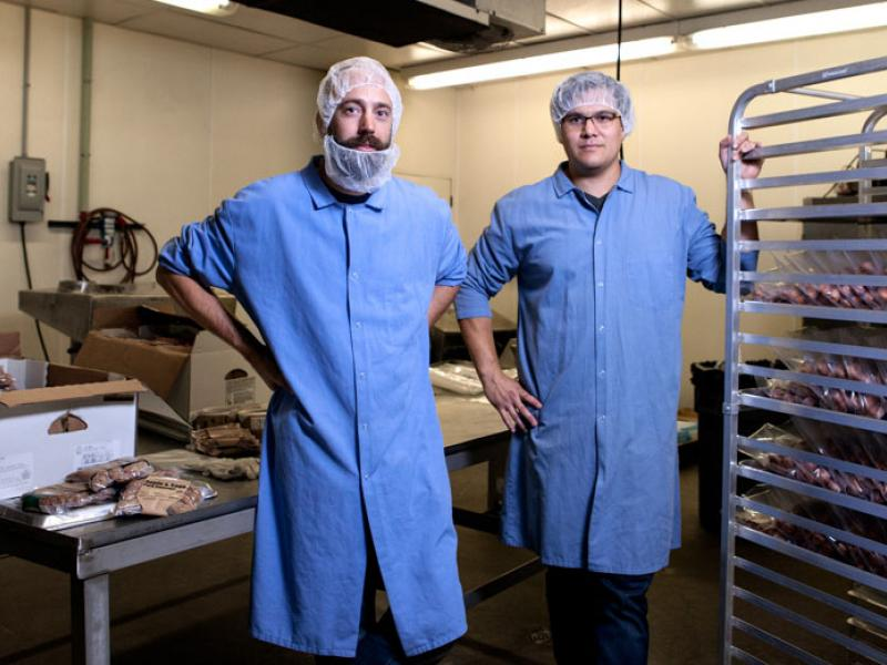 two men who are wearing long blue aprons and hair nets who are standing in a room with packaged meat around them
