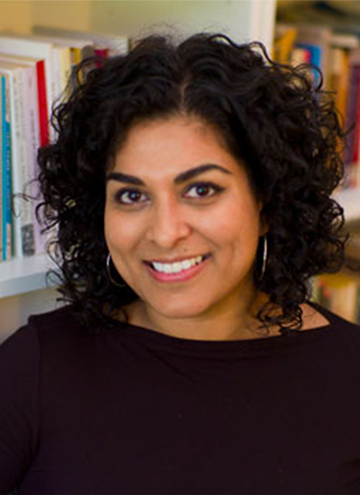 Photo of Divya Victor. Smiling young middle aged woman with curly black hair, wearing a black shirt.
