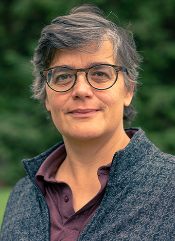 Photo of Ellen McCallum. Middle aged woman with glasses, short heathered black and grey hair, wearing a grey quarter zip.