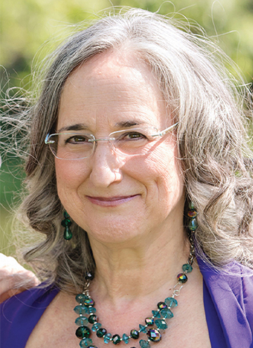 Photo of Ellen Pollak. Older woman with shoulder length curled grey hair, wearing glasses, a blue beaded necklace and a purple blouse.