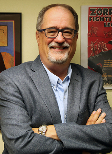 Photo of Gary Hoppenstand. Older middle aged man with glasses and arms crossed, wearing blue shirt with steel grey suit coat.