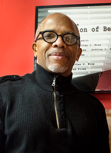 Photo of Jeff Wray. Older man with glasses and tight smile, wearing a black quarter zip sweater.