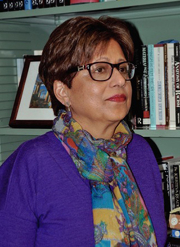 Photo of Jyotsna Singh. Older woman with short brown hair, glasses, a colorful scarf and purple shirt.