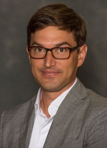 Photo of Kaveh Askari. Middle aged man with short brown hair, and glasses, and grey suit coat.