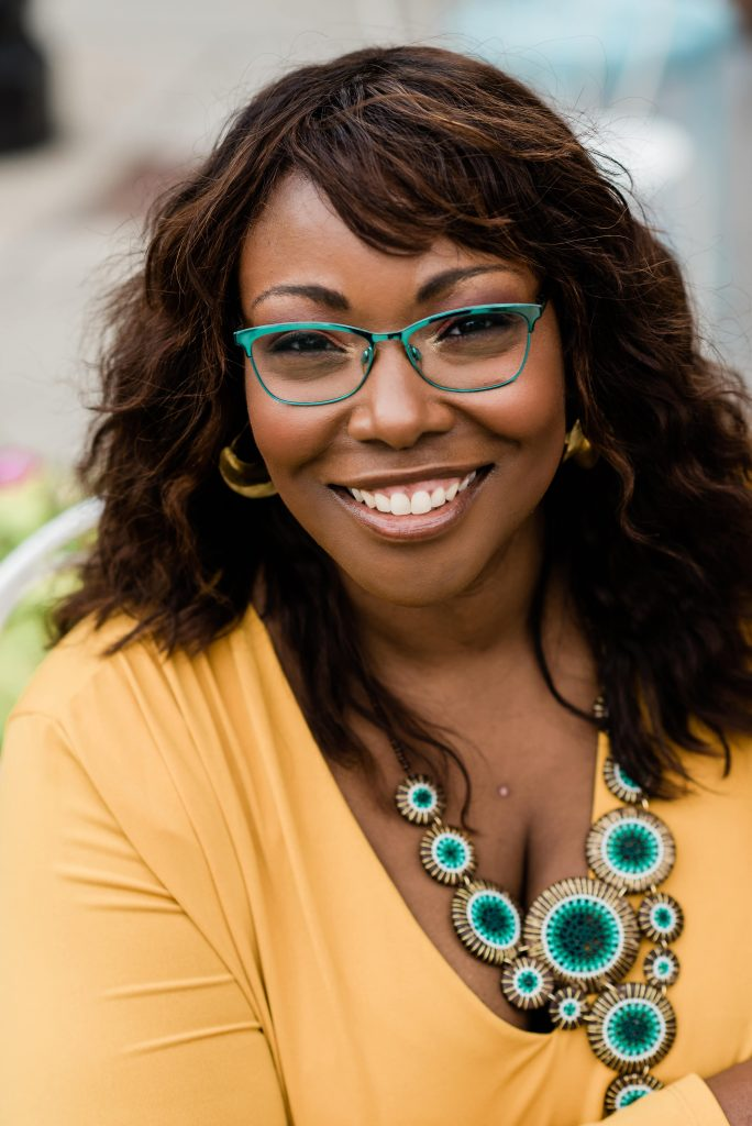 Women with wavy hair, yellow dress, and turquoise jewelry and glasses, looking at the camera smiling.