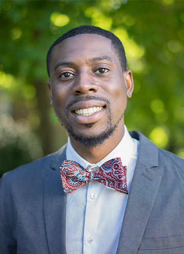 Photo of Lamar L. Johnson. Young man with big smile, wearing a colorful bowtie, blue shirt and grey suit coat.