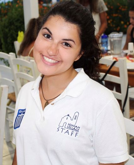 Young woman with titled head and dark hair and eyes, wearing a white polo, smiling at camera