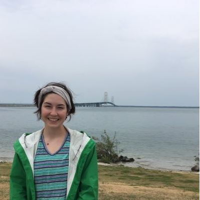 Young woman with short dark hair and headband, wearing a striped shirt and green jacket, smiling at camera with bridge and water in the background.