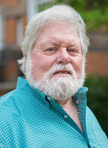 Photo of Patrick O'Donnell. Older man with white hair and beard. Wearing teal checkered button up.