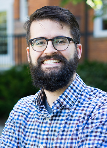 Photo of Peter Johnston. Young man with black hair and beard, glasses, and checkered blue button up.