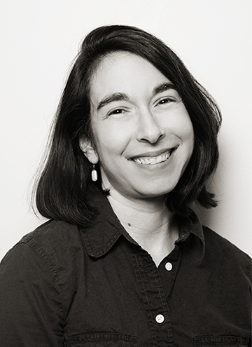Photo of Robin Silbergleid. Smiling young middle aged woman with shoulder length hair, wearing button up.