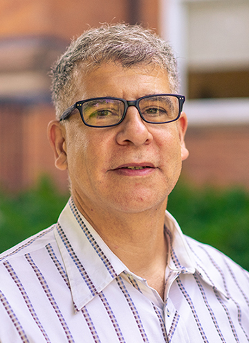 Photo of Salah Hassan. Portrait of older middle aged man with glasses, short grey hair, and wearing striped white button up.