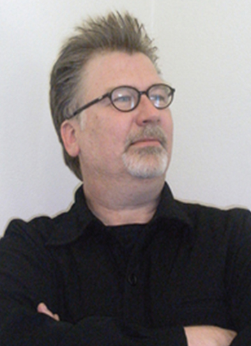 Photo of Scott Michaelsen. Older middle aged man with greyish brown hair and goatee, glasses, and black shirt.