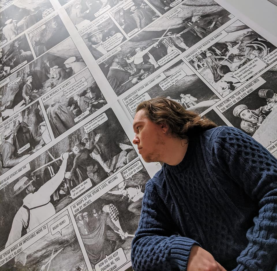 Man with long hair and blue sweater looking back at a black and white wall of comics.