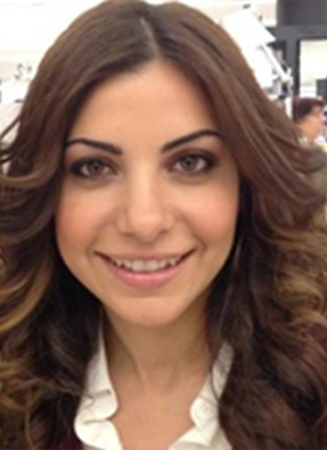Photo of Tamar Boyadjian. Portrait of smiling young woman with shoulder length brown curly hair.