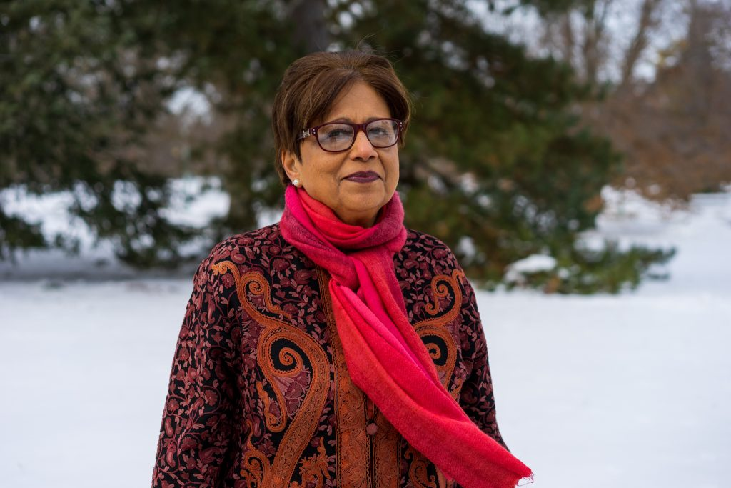 Woman with dark complexion in a snowy landscape wearing a red scarf and patterned jacket looking at the camera with a slight smile.