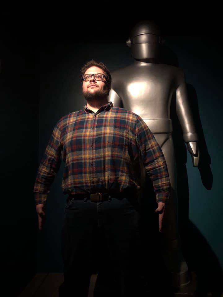 A man in a dark room wearing a plaid shirt standing in front of a robot statue and posing in a similarly statuesque manner.