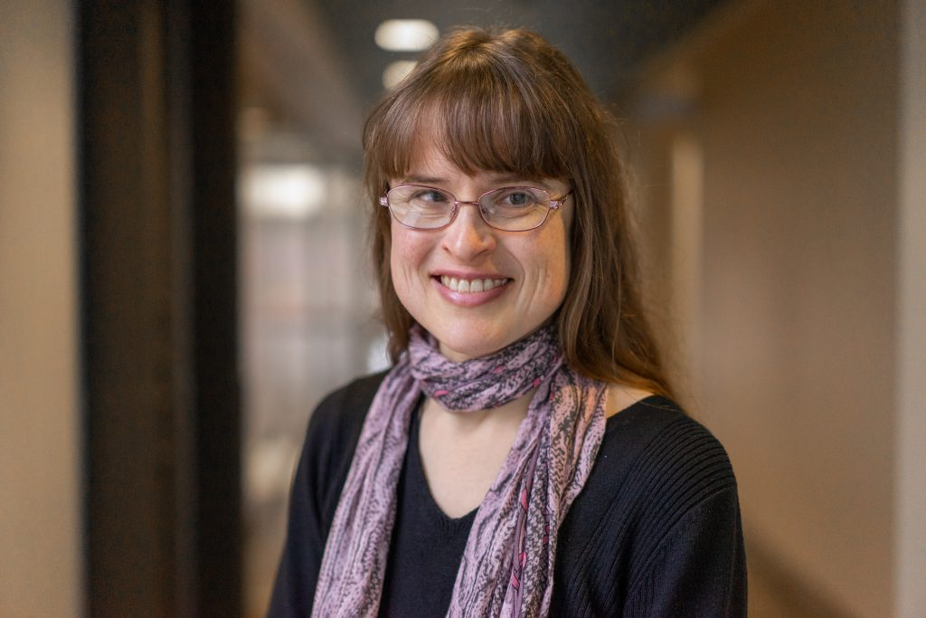 Woman with brown hair in black shirt, scarf, and glasses looking at the camera smiling.