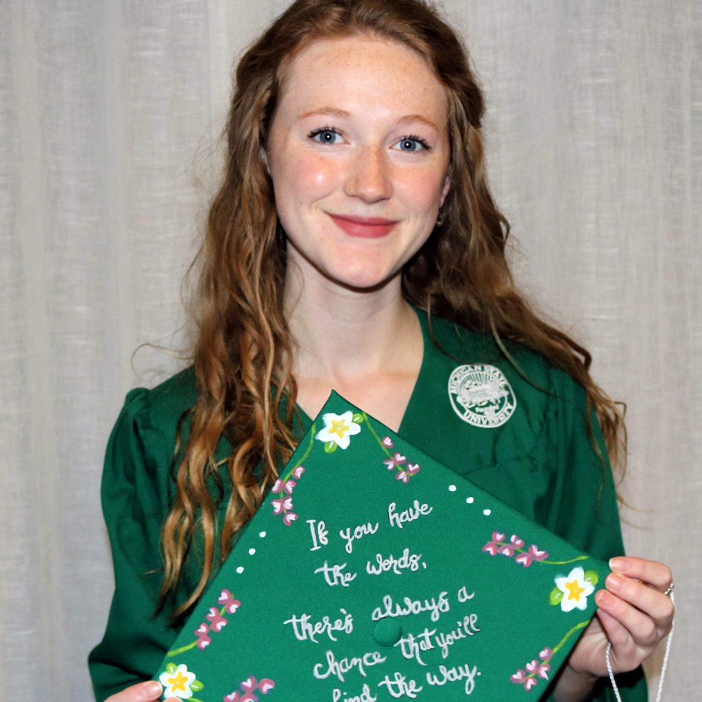 woman in a green graduation gown holding a decorated green cap