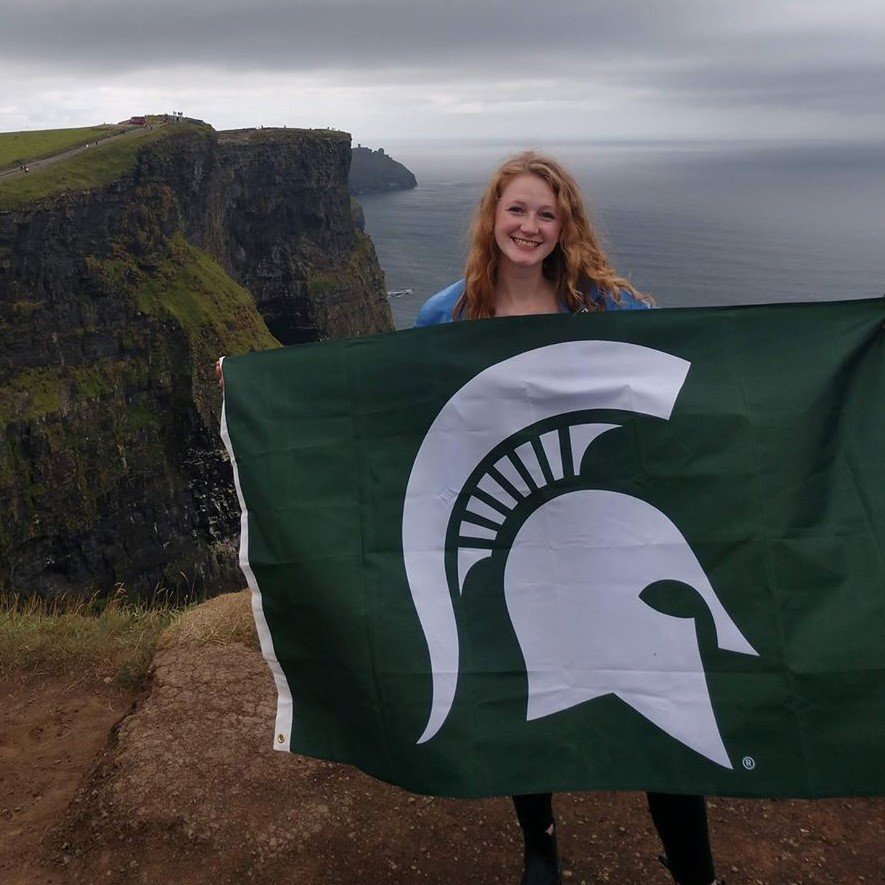 woman holding an MSU flag standing in front of a cliff looking to the ocean
