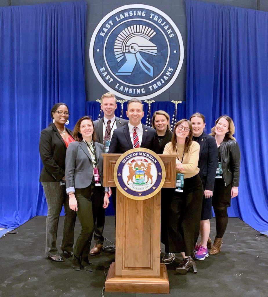 Eight people smiling, standing on a stage in front of a podium with a blue curtain behind them