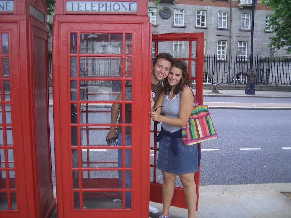 A man and a woman smiling, standing in a red telephone booth