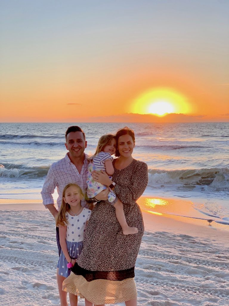 A man and woman with two children standing on a beach with a sunset behind them