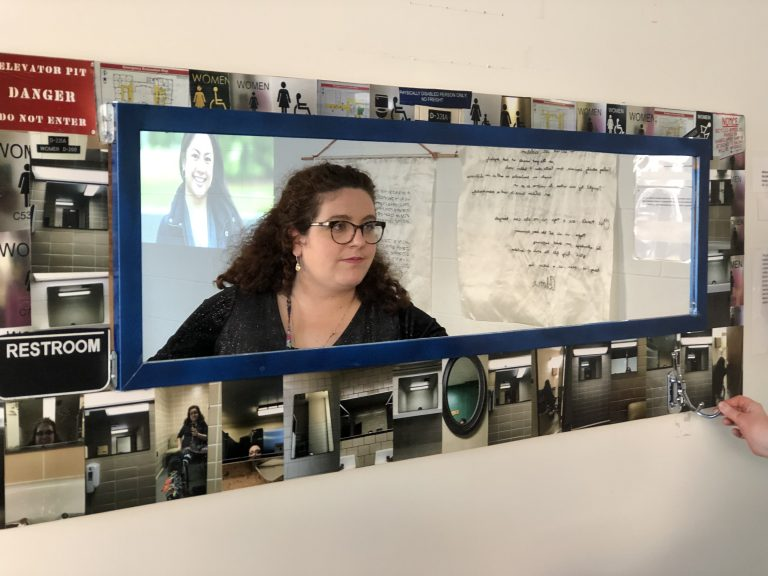 a women with curly hair wearing glasses  staring at her reflection in a long length mirror