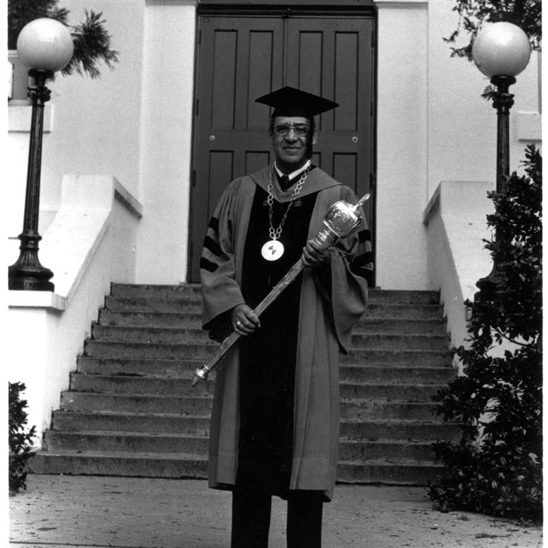 a black and white image of a man in a faculty grad cap and gown