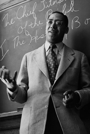 a black and white image of a man wearing glasses and a suit in a class room