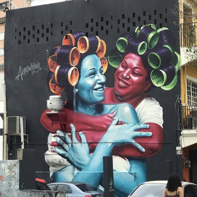 painting on a wall of a vlue woman and a pink woman embracing