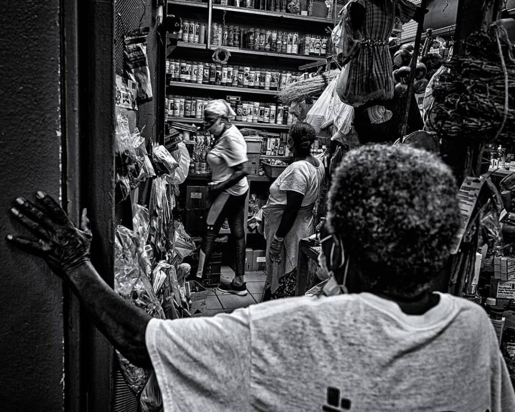 black and white image of someone looking into a room with the shelves stocked with things and people waiting in line
