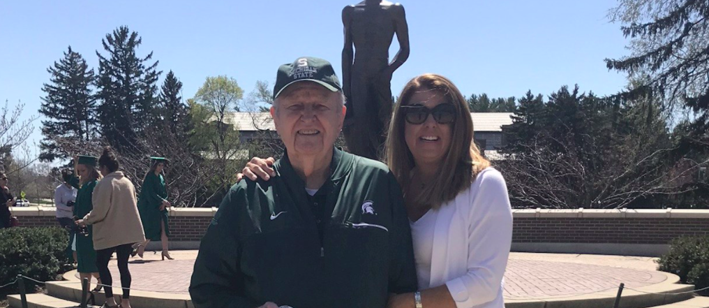 Man and woman standing side by side in front of the Spartan statue